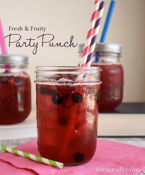 titled photo (and shown): Fresh and Fruity Party Punch (shown in a tall mason jar glass with red and blue striped straws)