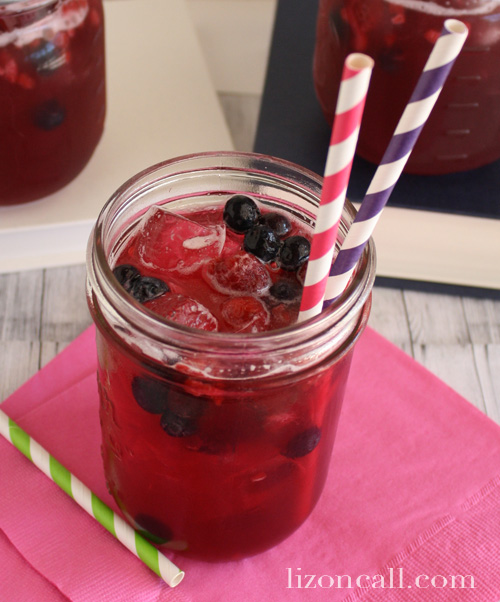 a glass of fresh fruit punch garnished with fresh berries and striped paper straws