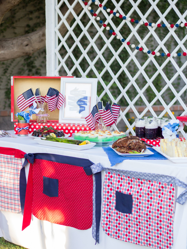 Using fun 4th of July half aprons, create a fun decoration for the front of your food table at your 4th of July party