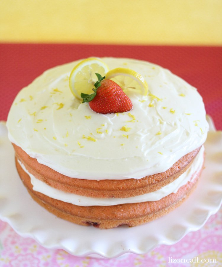 strawberry cake with fresh berries inside topped with creamy lemonade frosting - lizoncall.com