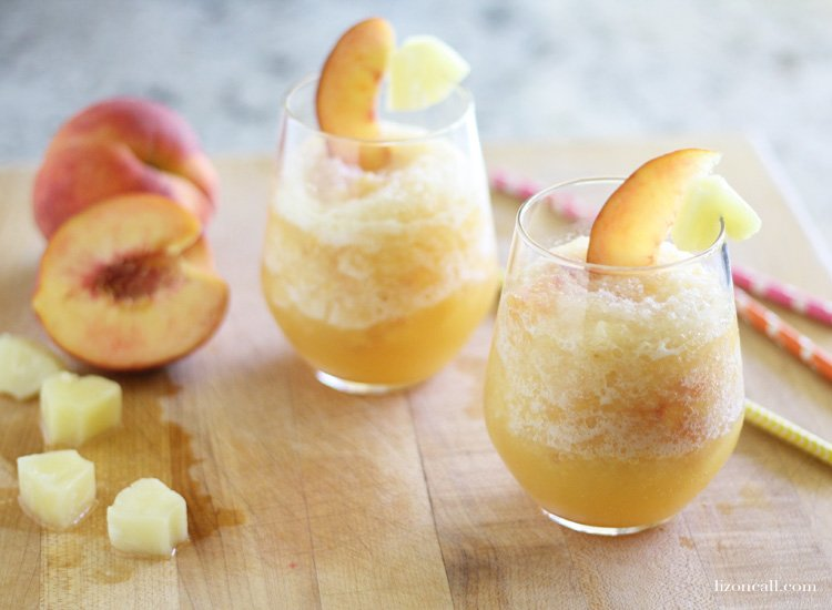 glasses filled with peach punch slush, garnished with fresh peach slices