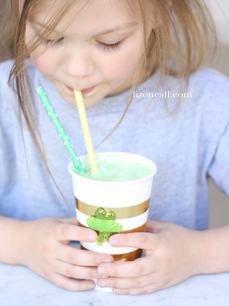 blonde haired little girl drinking a minty green party punch through a straw