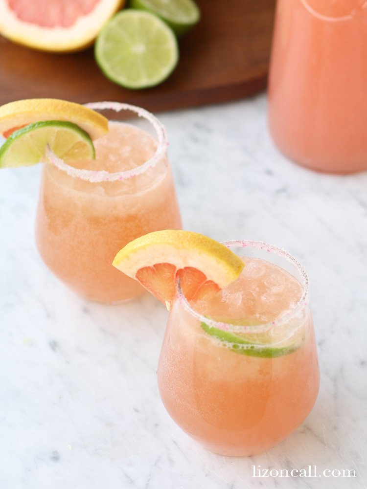 glasses of sparkling grapefruit juice punch garnished with fresh fruit slices