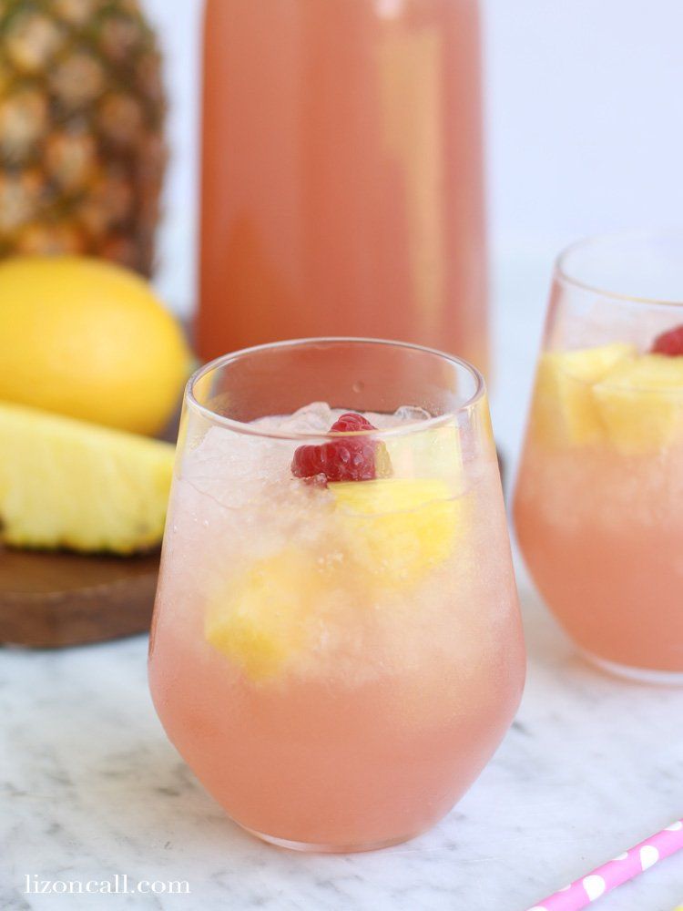 a glass of pink non-alcoholic punch garnished with fresh raspberries and lemon slices