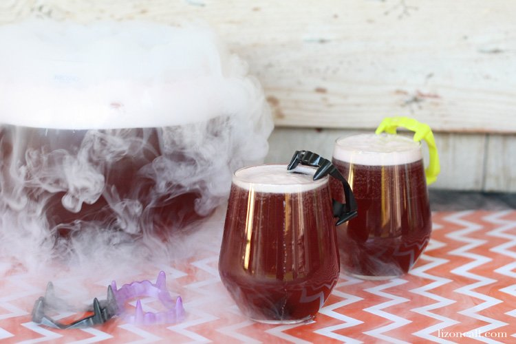 2 glasses of Black Magic Halloween Party Punch garnished with dry ice