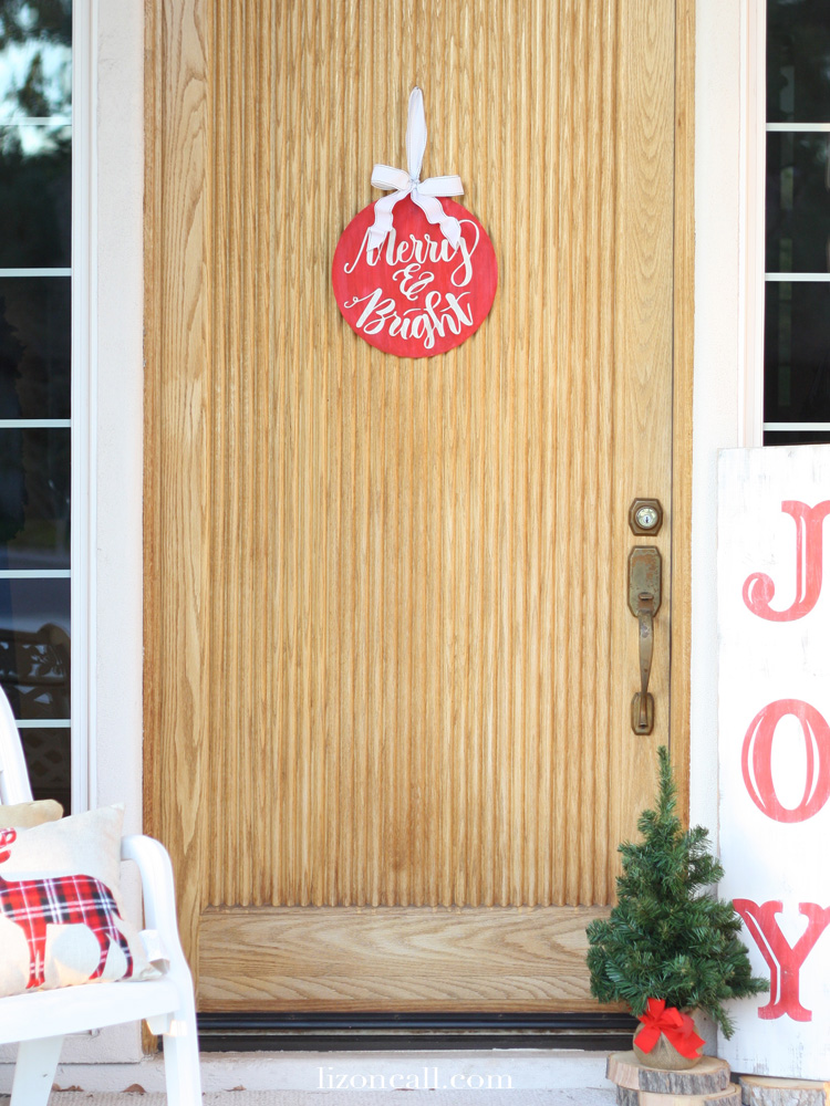 Dress up your front door this holiday season with this easy DIY front door ornament. Plus get this free merry and bright file to cut the pattern on your silhouette.