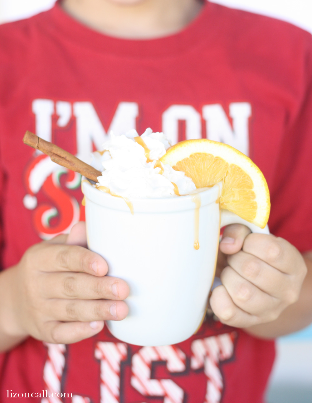 Child holding mug full of slow cooker holiday punch, topped with whipped cream and caramel sauce