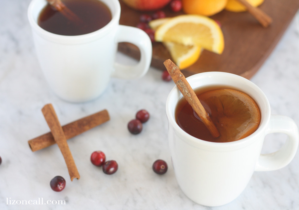 2 mugs filled with slow cooker holiday punch and garnished with cinnamon sticks