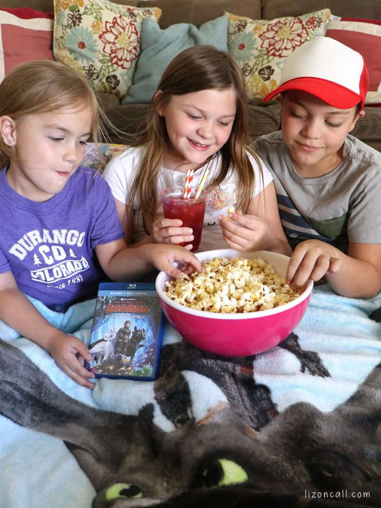 3 kids sitting on floor with big bowl of popcorn ready to watch How to Train Your Dragon 3 DVD Exclusive Gift Set from Walmart