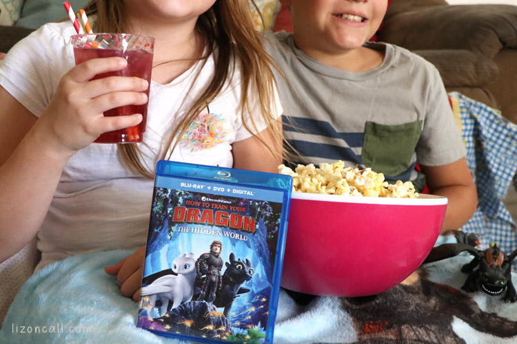 Close up of How to Train Your Dragon 3 next to a big bowl of popcorn with 2 kids. One holding glass of dragon party punch.