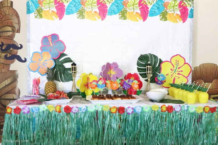 Food table decorated for a luau. Brightly colored with hibiscus flowers and leaves.