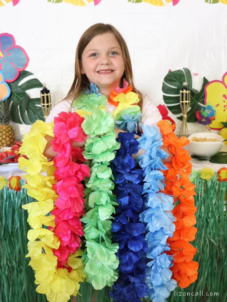 Girl holding multi colored hawaiian leis.