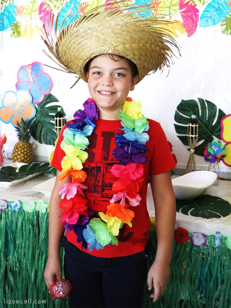 Boy wearing straw hat and hawaiian lei at luau party.