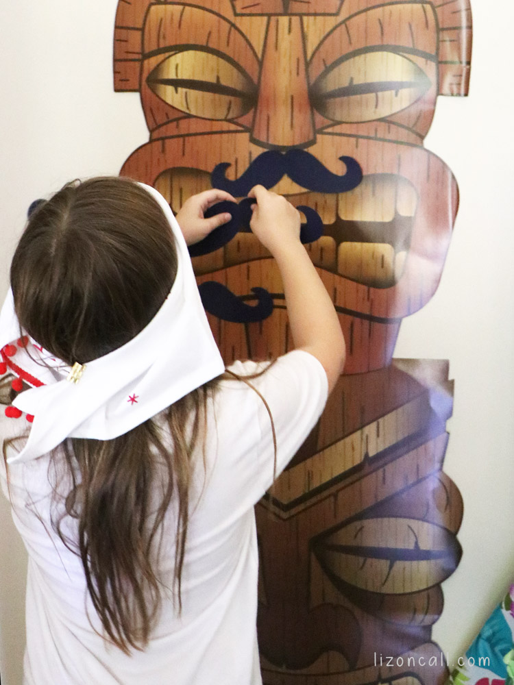 Girl blindfolded placing a large paper mustache on a tiki cut out. Party game