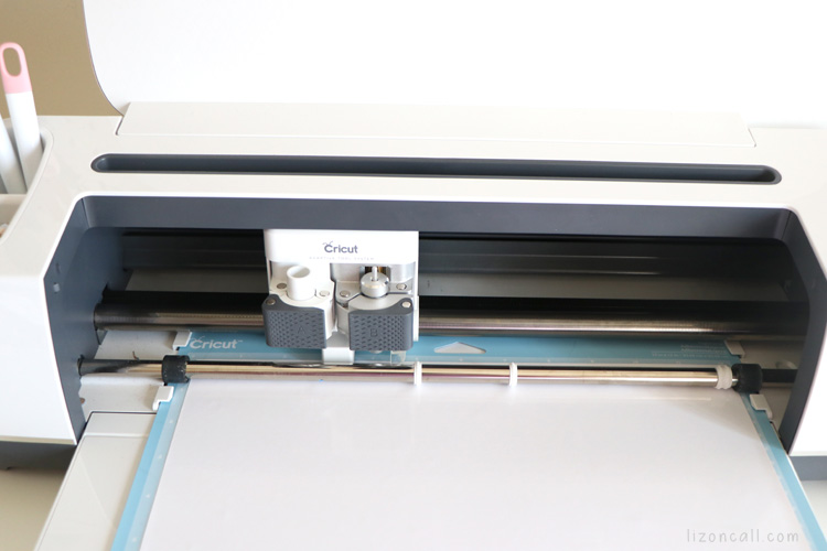 Cricut Maker machine loaded with mat that has iron on vinyl on it, ready to cut.