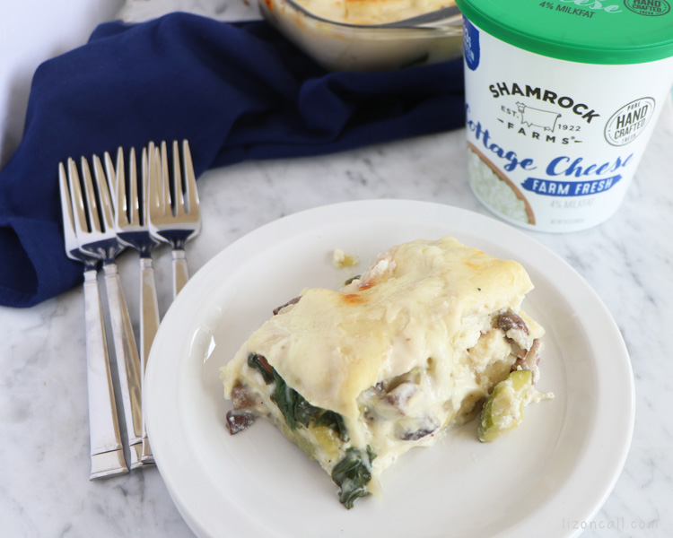Plated slice of white vegetable lasagna on a white plate next to a container of cottage cheese.