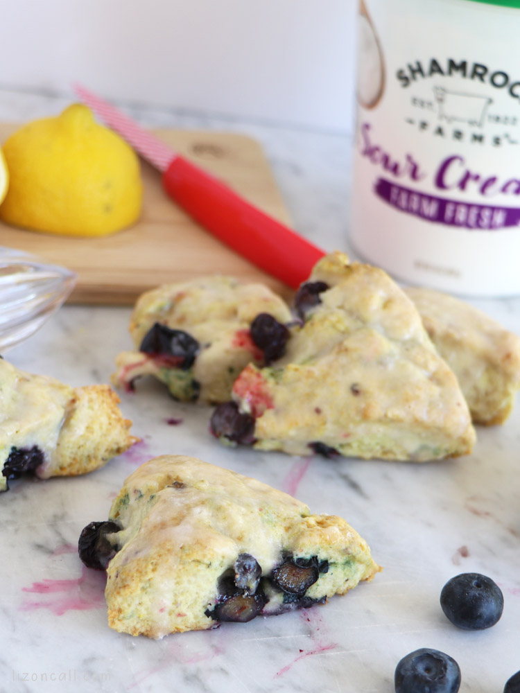 plated lemon blueberry scones next to sour cream container