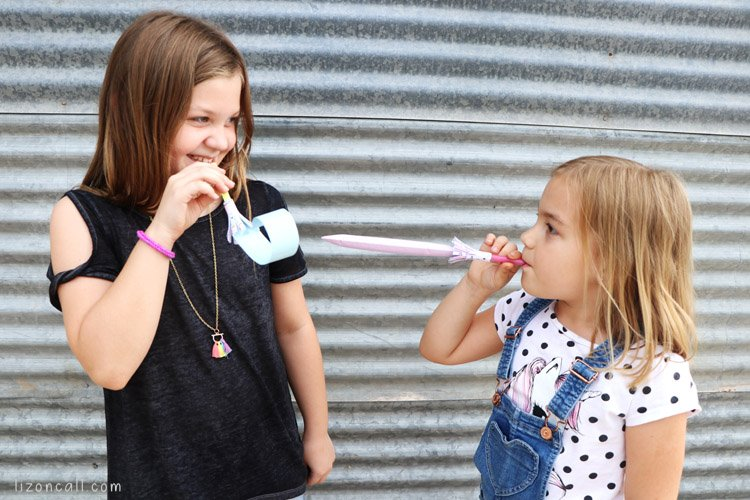 2 girls playing with party blowers