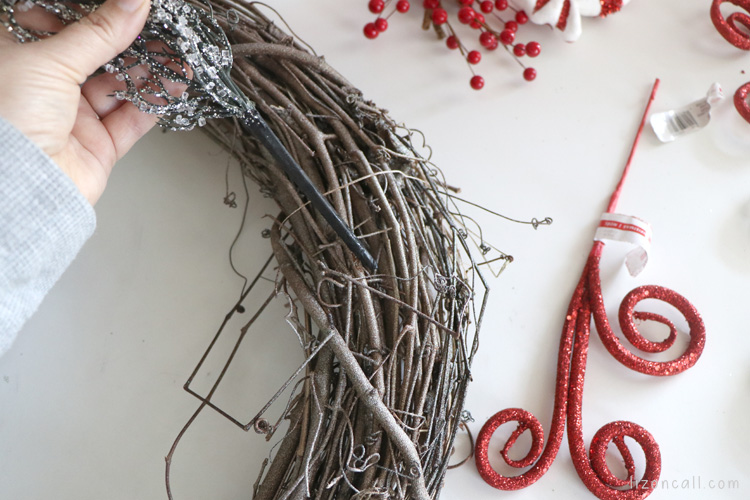 process image of inserting decorative pick into grapevine wreath
