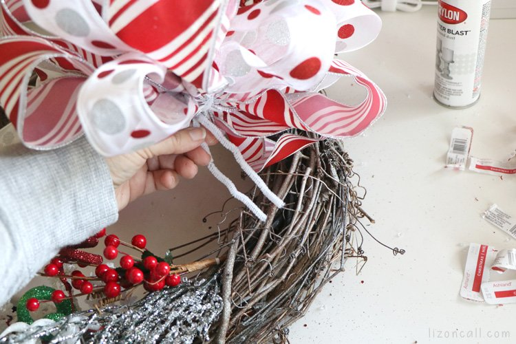 Process shot of adding double ribbon bow to a holiday wreath