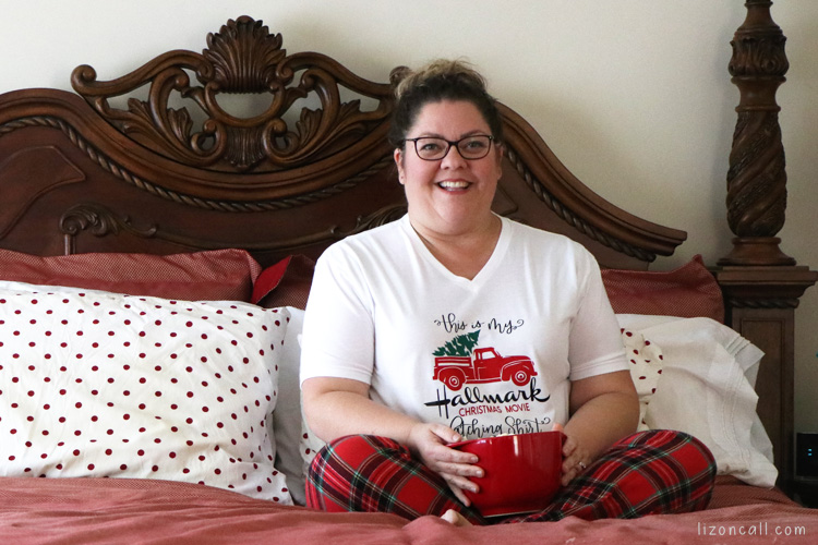 Women wearing Christmas movie watching shirt in bed