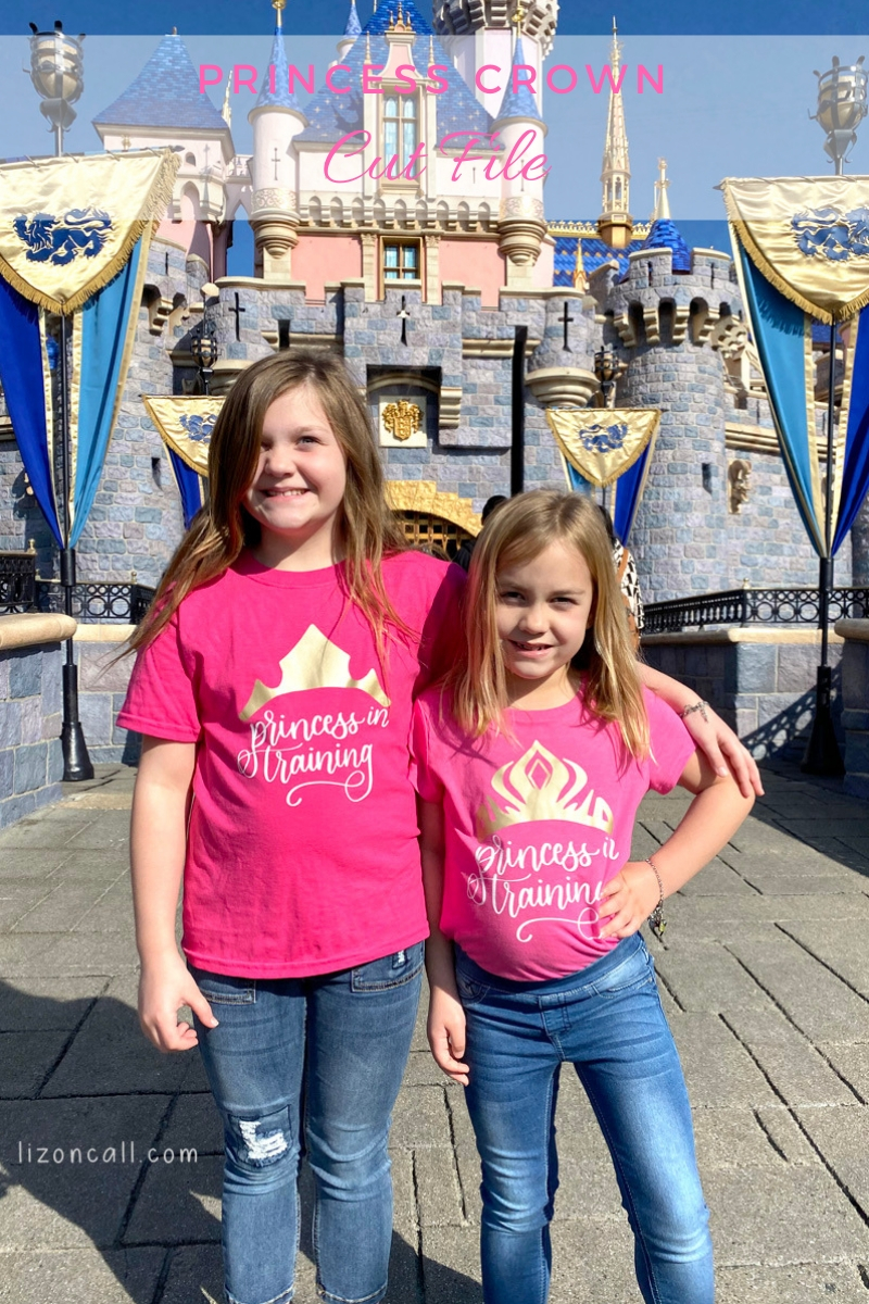 2 girls wearing princess in training shirts in front of the castle